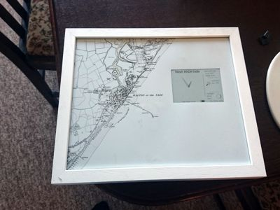 A photo frame containing a map of Walton-on-the-Naze and an electric ink display indicating the next high tide
